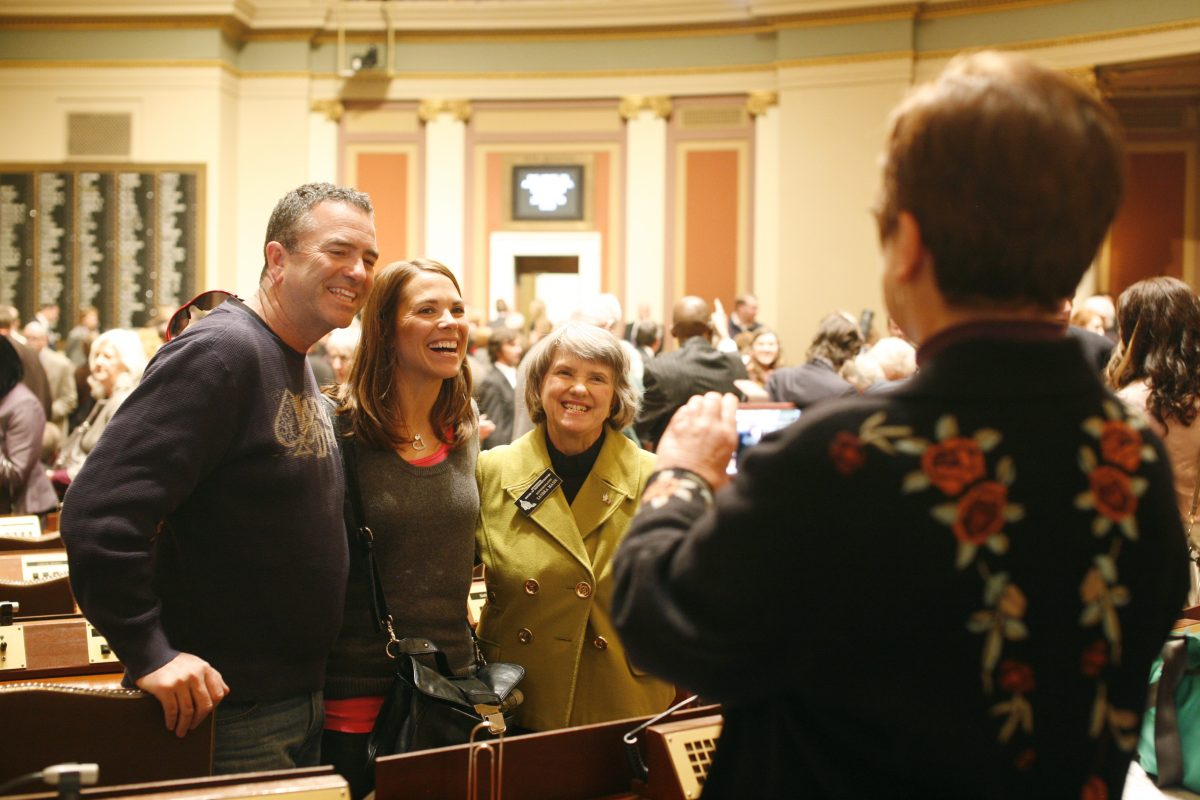 Rep. Alice Hausman takes a photo of Rep. Sandra Masin and her family